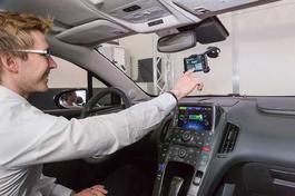 Junger Mann hinter dem Steuer bedient einen Touchscreen